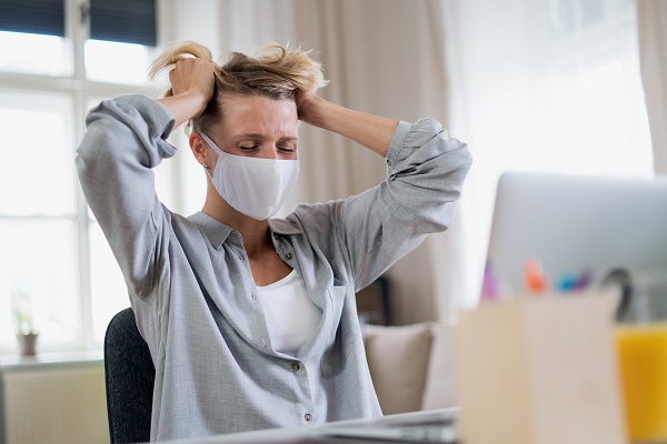 Woman indoors in office feeling stressed, mental health and coronavirus concept.